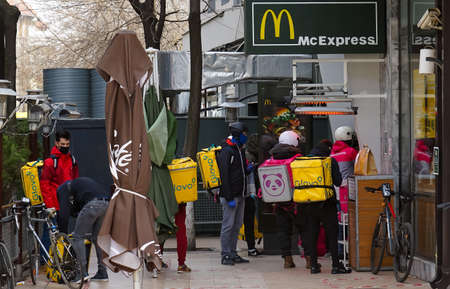 Bucharest, Romania - March 26, 2020: Glovo food delivery couriers queue at a McDelivery window of McDonald's, delivery being the only allowed during the state of emergency due to coronavirus. Redakční