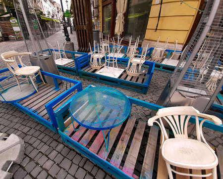Bucharest, Romania - May 05, 2020: Tables and chairs are stored in front of a restaurant temporary closed during the state of emergency due to coronavirus in the Old Town of Bucharest.