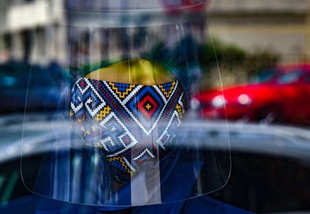 Bucharest, Romania - May 07, 2020: A face shield and a cotton made respirator mask printed with a colorful Romanian folk pattern are displayed on a mannequin in the window of a handmade clothing store.