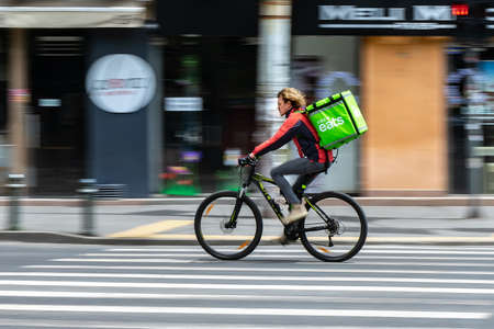 Bucharest, Romania - May 07, 2020: An Uber Eats food delivery courier on a bike in high speed. Restaurants are closed and only deliveries are allowed during the state of emergency due to coronavirus.