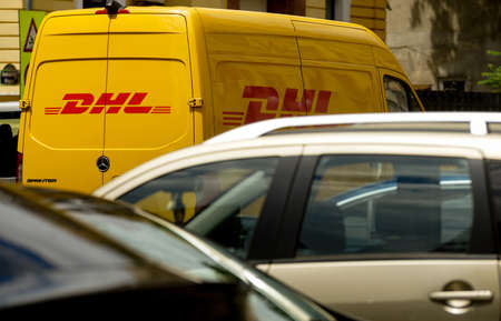 Bucharest, Romania - May 25, 2020 An yellow DHL delivery van is seen on a street in downtown Bucharest. This image is for editorial use only. Redakční