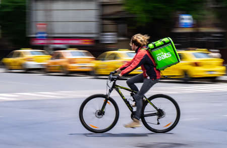 Bucharest, Romania - May 07, 2020: An Uber Eats food delivery courier on a bike in high speed. Restaurants are closed and only deliveries are allowed during the state of emergency due to coronavirus. Redakční