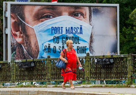 Bucharest, Romania - July 13, 2020: A woman walk in front of an advertisement, part of a campaign paid by the Romanian Government, on which is written Wear mask with the thought that she will be fine.
