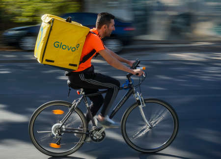 Bucharest, Romania - September 27, 2020: A Glovo food delivery courier on a bike in high speed in traffic on a boulevard in Bucharest. Sajtókép