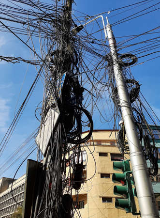 Bucharest, Romania - September 20, 2020: Many internet and communications cables hang out on pillars in Bucharest.