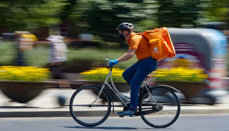 Bucharest, Romania - August 04, 2020: A Takeaway food delivery courier on a bike in high speed in heavy traffic on a boulevard in Bucharest. Sajtókép