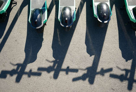 Bucharest, Romania - July 30, 2020: The shadow of Bolt electric scooters parked on a sidewalk in Bucharest. This image is for editorial use only.