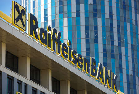 Bucharest, Romania - August 16, 2021: A logo of Raiffeisen Bank, Austrian multinational banking and financial services corporation, is displayed above a building office, in Bucharest, Romania. Sajtókép