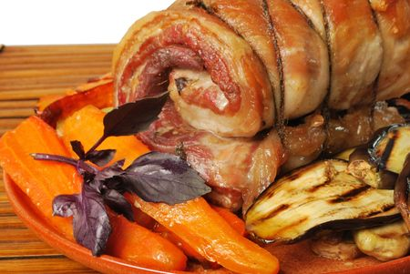 Pork roll prepared and served with carrot and aubergine Stock Photo
