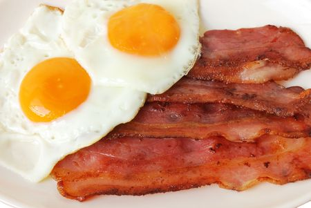 Fried eggs with bacon on white plate Stock Photo