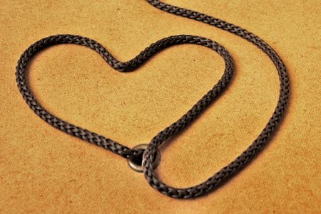 Rope heart on rough brown background Stock Photo