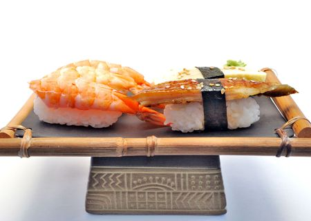 Sushi on ceramic dish on white background