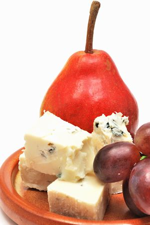 Plate with cheese, pear and grapes on white