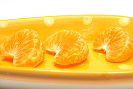 Tangerine segments on orange dish on white Stock Photo
