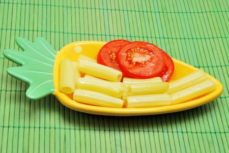 Macaroni and tomatoes on funny plate on green