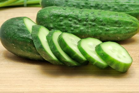 Whole and sliced cucumbers on wood cooking board