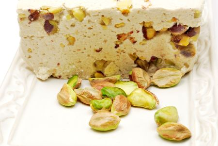 Halva with pistachios on plate on white background Stock Photo