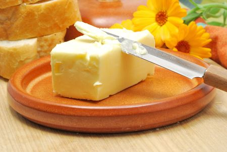 Butter on ceramic plate on kitchen table Stock Photo