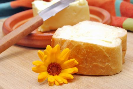 Bread and butter with flower on kitchen table Stock Photo