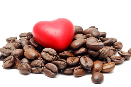 Heap of coffee beans with heart on white background