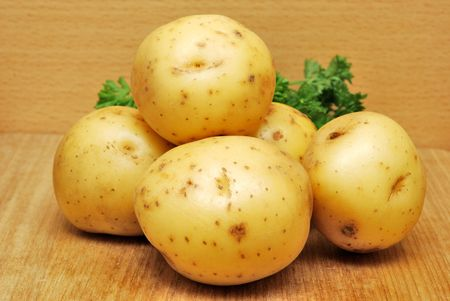 Fresh raw potatoes on wood kitchen table Stock Photo
