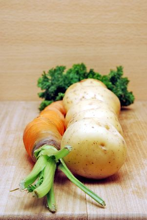 Potato and carrot with parsley on wood kitchen board