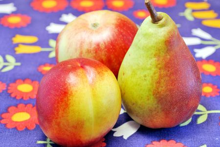Nectarine, apple and pear on color kitchen tablecloth Stock Photo
