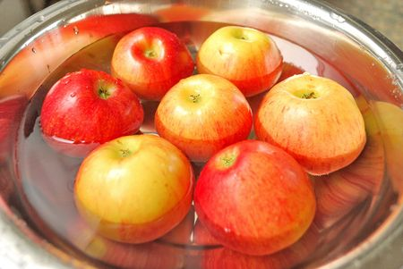 Bright apples in metal dish with water  Stock Photo