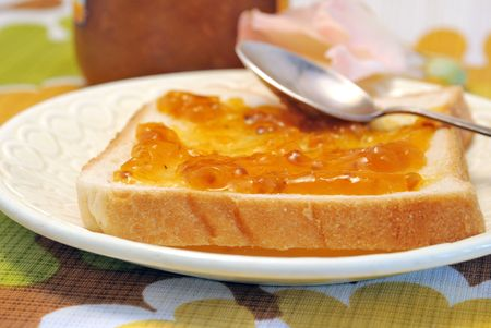 Cloudberry jam on wheat bread with spoon Stock Photo