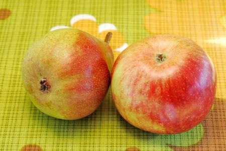 Pear and apple on color kitchen tablecloth