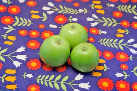 Green apples on color kitchen tablecloth