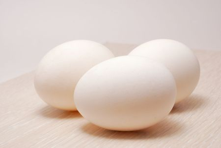 Three eggs on white tinted wood Stock Photo
