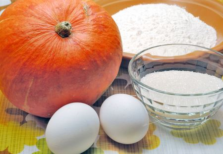 Pumpkin, apple, eggs and flour on kitchen table Stock Photo