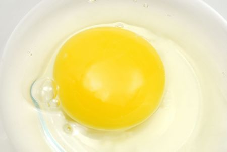 Raw egg in glass bowl