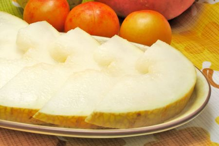 Sliced melon served on plate on kitchen table Stock Photo