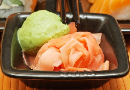 Wasabi and ginger in metal bowl on bamboo mat