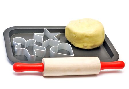 Baking cups, rolling pin and pastry on tray Stock Photo