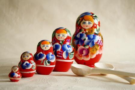 matryoshkas: Row Russian Matryoshkas and two wooden spoons. Stock Photo