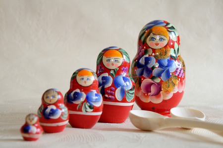 Row Russian Matryoshkas and two wooden spoons. Stock Photo