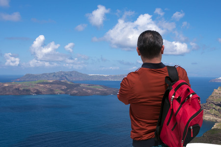 A red backpack is standing on the sea. Removes a beautiful landscape on your mobile. Beautiful morning.
