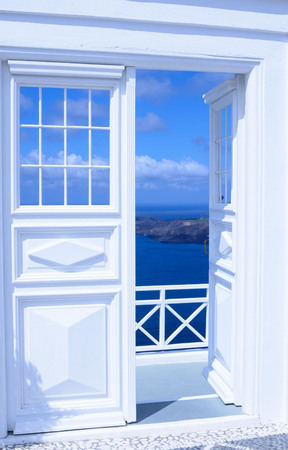 White wooden light open door. Behind the door is a beautiful turquoise sea and mountains. Sunny morning on the Greek island of Santorini. Stock Photo - 122799515