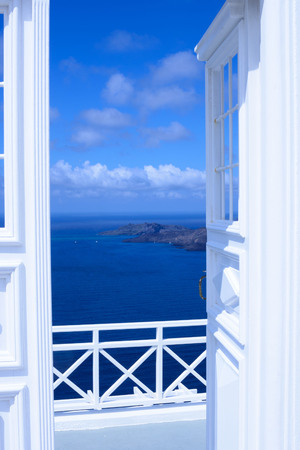 White wooden light open door. Behind the door is a beautiful turquoise sea and mountains. Sunny morning on the Greek island of Santorini.