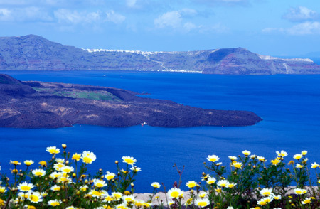 Summer sunny morning on the island of Santorini, Greece. Blue sea, blue sky with clouds against the background of the island. Euro trip. Stock Photo