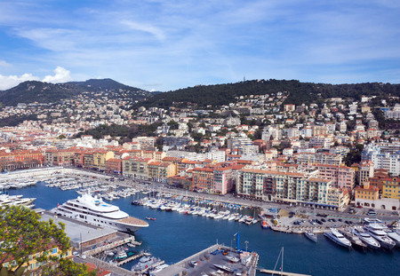 Nice, France, March 2019. Port of the French city of Nice. Private yachts and boats are parked near the coast. Beautiful mountains, the port, the lighthouse and the turquoise sea - a great place to relax. Standard-Bild - 122809955