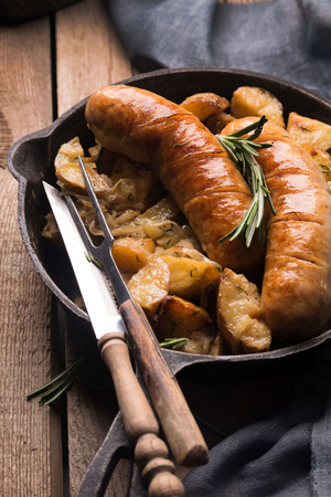 Delicious hot hearty food: fried potatoes with sausages on the grill in a cast iron pan. Knife and fork with wooden handles. High calorie lunch. Traditional German cuisine.