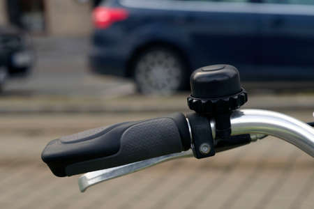 Black rubber handle at the helm of the bike and bell. Close-up. Ecological transport in the city is becoming increasingly popular.