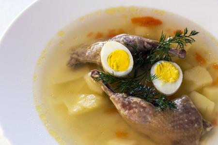 Deliziosa zuppa profumata a base di brodo di quaglia in un piatto da pranzo bianco. Fette di carne, uova di quaglia, aneto, bulgur, pepe e cracker - un piatto utile e semplice. Cucina turca.