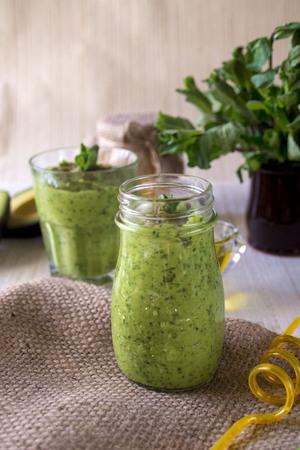 Dikke voedzame smoothies, waaronder: avocado, appel, banaan, spinazie, sinaasappelsap, honing, lijnzaad, munt en olijfolie. Goede voeding. Gezonde levensstijl.