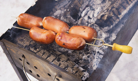 Beautiful, juicy, tasty and fragrant sausages on the grill roasting over coals at a picnic in the winter forest. Around soars smoke and aroma. Meeting with friends.