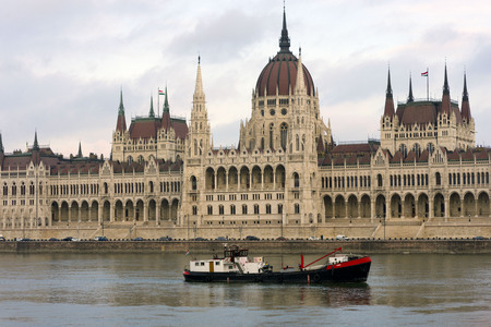 Cargo ship sailing on the Danube. Barge on the background of the Parliament, famous sights of Budapest on a cloudy day.
